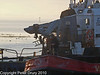 16 Nov 2010 - Dawn loading at Aggregates Wharf, Langstone Harbour. Copyright Peter Drury 2010<br /> The tug and barge leave the wharf with a seaman tidying up the decks.<br /> E5 + Sigma 50-500, ISO 800, f8, Aperture Priority