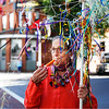 Barbara Raon, of Bennington surrounded by ribbons and streamers plays her kazoo in harmony with the dozens of instruments played by community members at the four corners in Bennington.