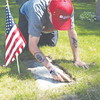 Vietnam veteran J. Barry Neas digs out grass from the perimeter of a veteran?s grave Monday. The Lancaster resident spent more than five hours planting flags and sprucing up veterans? graves at Leominster?s Evergreen Cemetery.<br /> SENTINEL & ENTERPRISE / Jordan Tillery