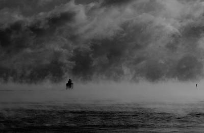 Lighthouse in winter lake mist.