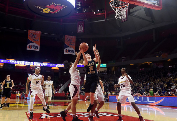 Teutopolis' Olivia Niemerg (15) drives to the basket between Chicago Marshall defenders during the awards ceremony after being defeated by Chicago Marshall in the IHSA Class 2A Girls basketball state championship game at Illinois State University's Redbird Arena Saturday evening.  Chet Piotrowski Jr. photo/Piotrowski Studios