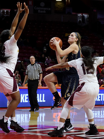 Teutopolis' Sadie Bueker (10) attempts a shot over Chicago Marshall's Brandi Hudson (14, left) and Jalyn Jimenez (12, right) during the IHSA Class 2A Girls basketball state championship game at Illinois State University's Redbird Arena Saturday evening.<br /> <br /> Chet Piotrowski Jr. photo/Piotrowski Studios