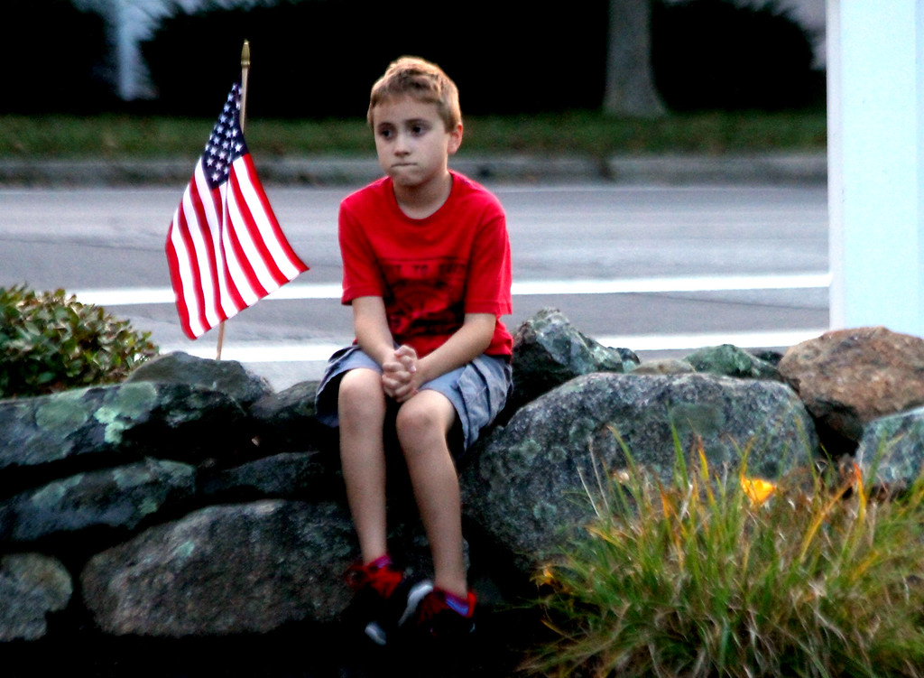 . This lone boy (no Id), sits and reflects at the Tewksbury 9-11 Memorial. SUN Photo by David H. Brow