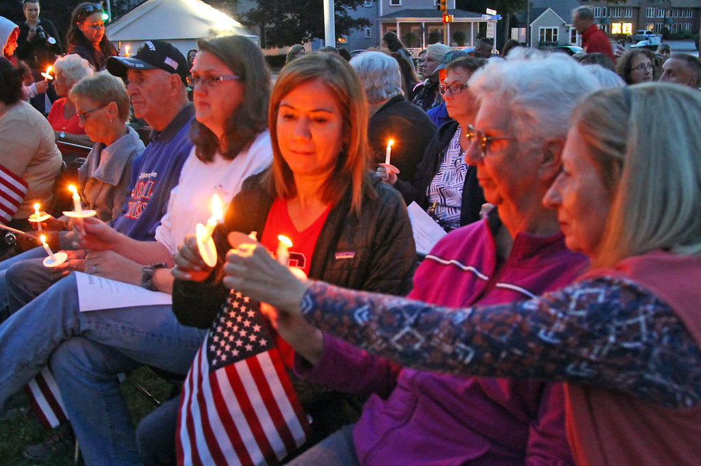 . People lighting candles at the Tewskbury 9-11 Memorial. SUN Photo by David H. Brow