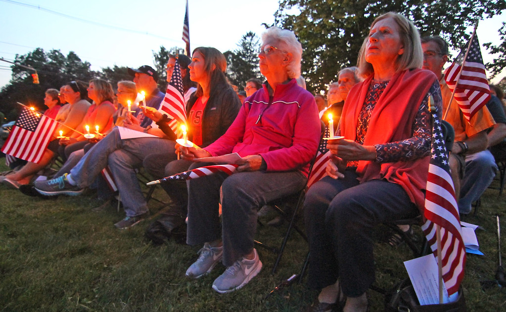 . People with lit candles at the Tewksbury 9-11 Memorial. SUN Photo by David H. Brow
