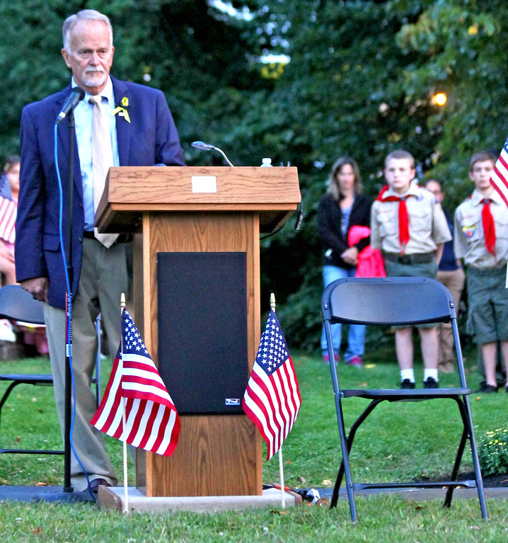 . Robert Fowler, President of th 9-11 Committee and MC of the Tewsbury 9-11 Memorial event, talks about Fred Simon and places a empty chair in memory of him. SUN Photo by David H. Brow