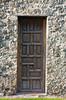 A wooden door at the Mission Concepcion building exterior facade in San Antonio, Texas, USA.