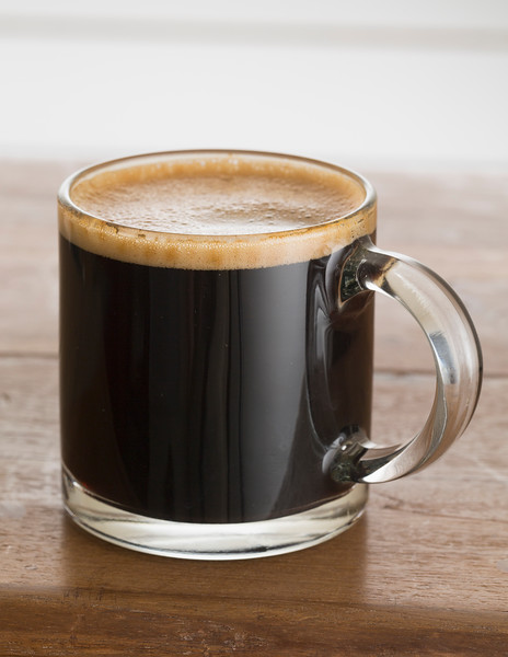 Black coffee and froth in glass mug wood table