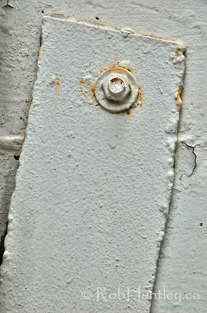 Bolt holding a metal plate on a concrete wall.   © Rob Huntley