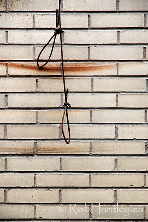 Cables for controlling exterior building vents leaving rust marks on an off-white wall.   © Rob Huntley