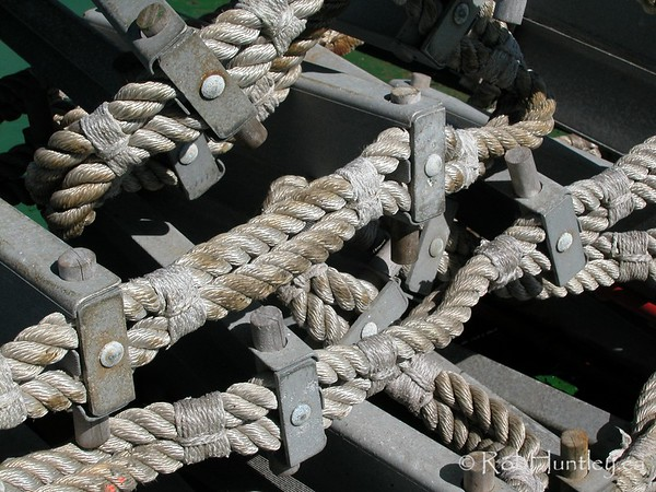 Rope ladder folded on the deck of a boat.