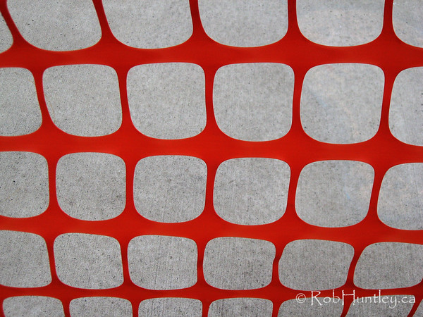 Abstract image of an orange snow fence pattern against a concrete walkway.  © Rob Huntley