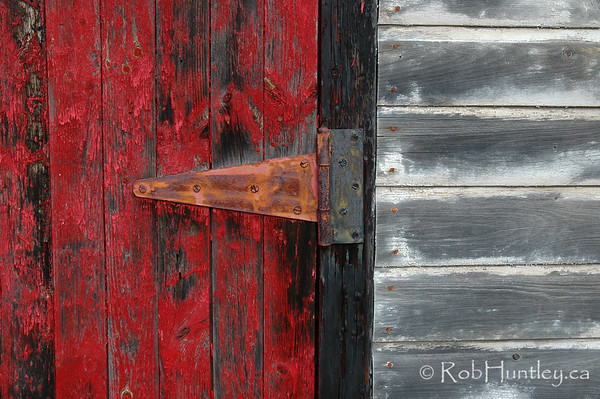 Door hinge and flaking red paint on a shed door.