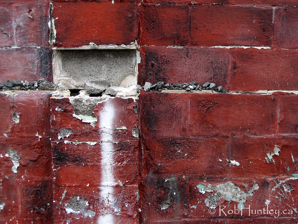 Crumbling wall and peeling red paint.