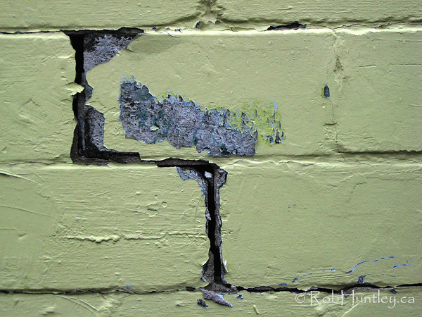 Cracks between concrete blocks and peeling yellow paint.