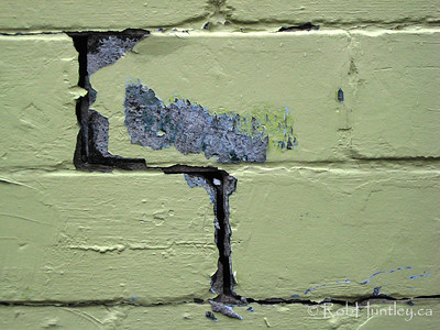 Cracks between concrete blocks and peeling yellow paint on a demolition site in Westboro, Ottawa.  © Rob Huntley