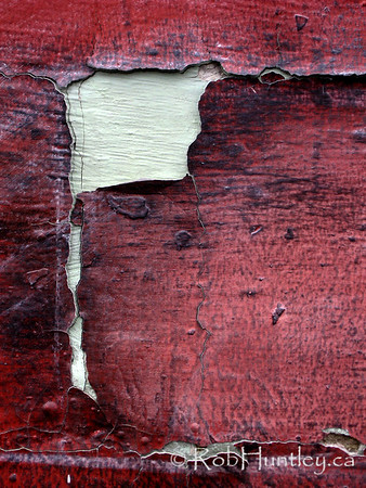 Peeling red paint on a concrete block wall.