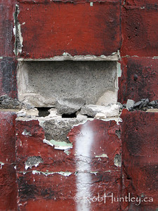 Red peeling paint on a concrete block wall in Westboro, Ottawa.  © Rob Huntley
