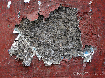 Peeling red paint and crumbling concrete block on a concrete block wall in Westboro, Ottawa.  © Rob Huntley