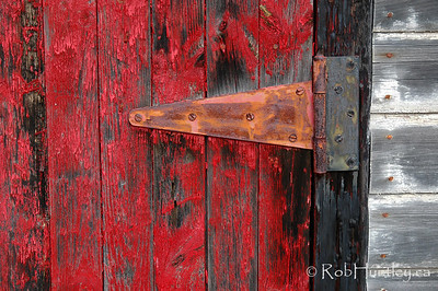 Door hinge and flaking red paint on a shed door.  © Rob Huntley