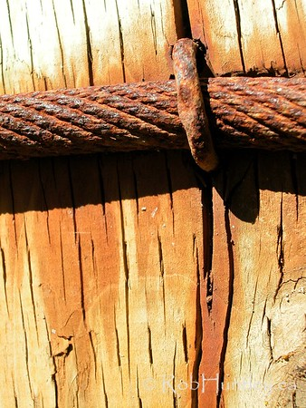 Rusty cable stapled to a post  © Rob Huntley