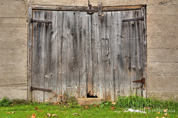 Sagging Barn Door.  Barn door with sagging frame on a poured concrete wall.  © Rob Huntley