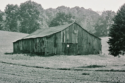 Weathered wooden barn at dusk in Tennesee.  Wonder what the sign says?