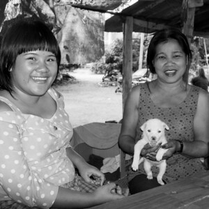 Two ladies with white puppy, on the road to Ban Pong.