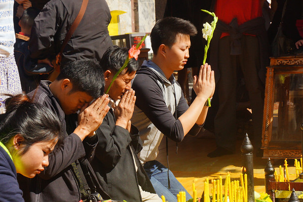Three people praying at Doi Suthep Temple