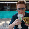 Nomadic Samuel Jeffery drinking a coconut shake and displaying an Indian curry at Pun Pun vegetarian restaurant in Chiang Mai, Thailand.