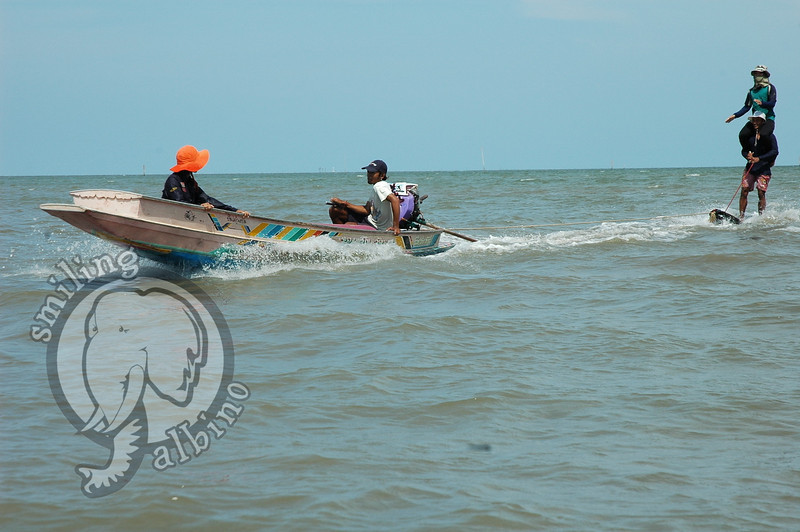 Skiing from a longtail boat on the wooden sled they use in the water/mud