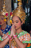 A Thai girl in ethnic dress perfoms a traditional buddhist dance at the Erawan shrine in downtown Bangkok, Thailand, Asia.