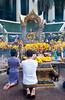 Worshipping the buddha image at the Erawan shrine in downtown Bangkok, Thailand, Asia.