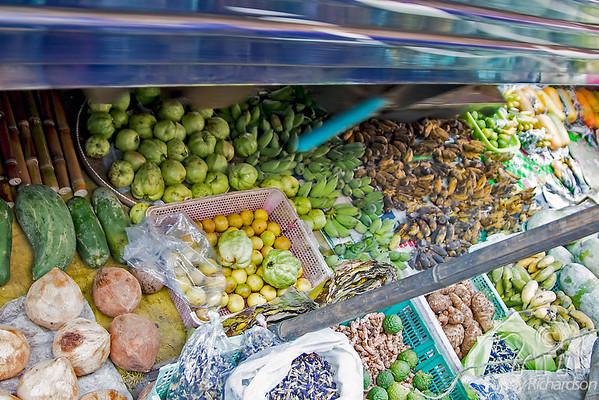 Train passing over fruit pulled back at Maeklong Railway Market