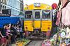 Train passing over Maeklong Railway Market