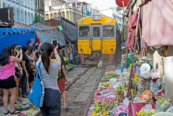 Tourists taking pictures as the dust falls on Maeklong Railway Market
