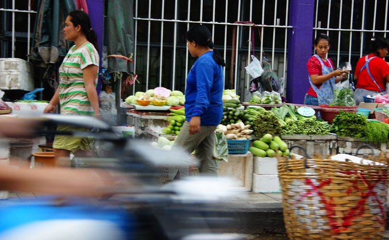 Thai ladies set up market just as a motorist zooms past them on the street - Bangkok, Thailand