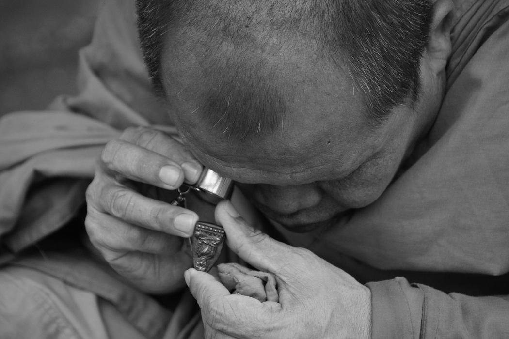 Thai Monk peering through an eyepiece in Bangkok, Thailand
