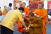 Buddhist monks line up early in the morning to recieve alms from Thai citizens in the parking lot of the Marble Temple in Bangkok, Thailand, Asia.