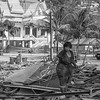 Woman scavenging through the rubble after the army demolished Surin Beach Vendors