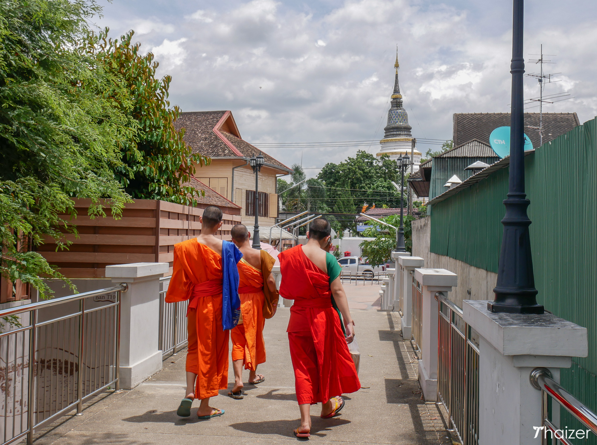 monks walk across the Chansom Memorial Footbridge in Chiang Mai