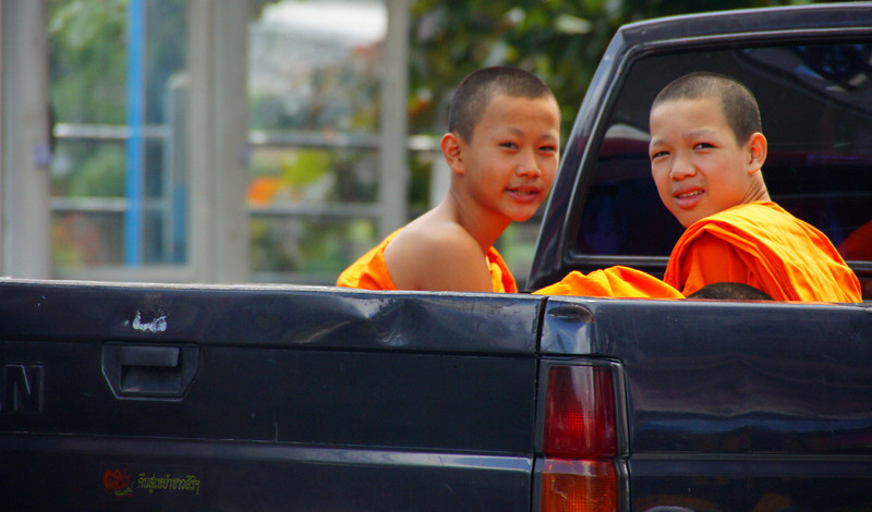 Today's daily featured travel photo is of a couple of young smiling Thai monks in the back of a pick-up truck in the heart of Chiang Mai, Thailand.