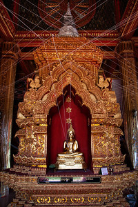 White strings attached to Buddha's wrist to spread the blessing during prayer in Thailand.
