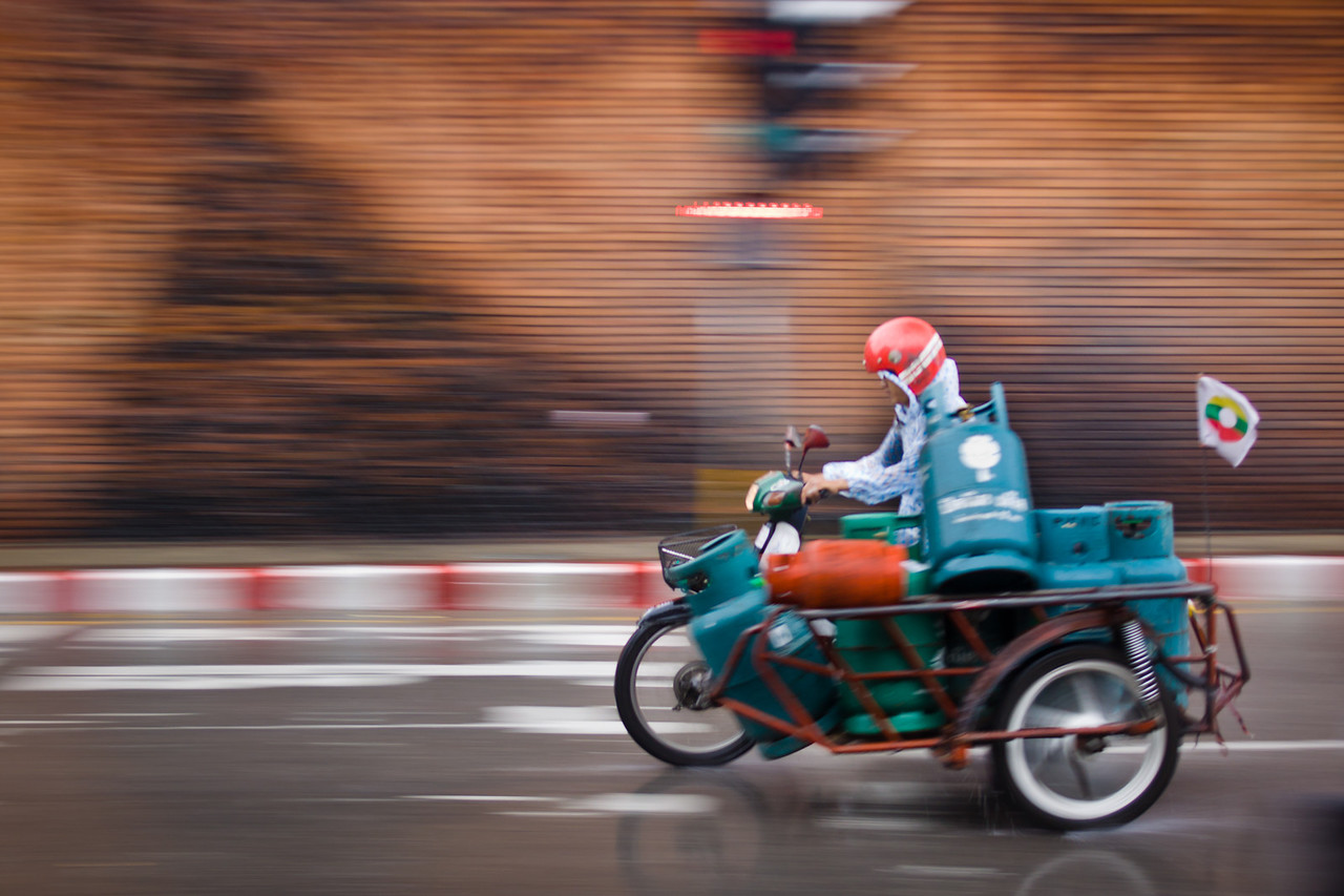 A speeding scooter carrying gas tanks in Chiang Mai, Thailand.