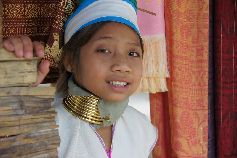 A cute girl from the Karen Hill tribe (long-neck) poses with a lovely smile in her village nearby Chiang Rai