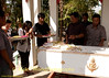 Relatives Place Offerings On the Coffin