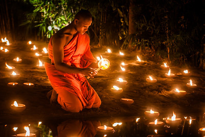 A monk lighting candles during the Loy Krathong Festival in Chiang Mai, Thailand.