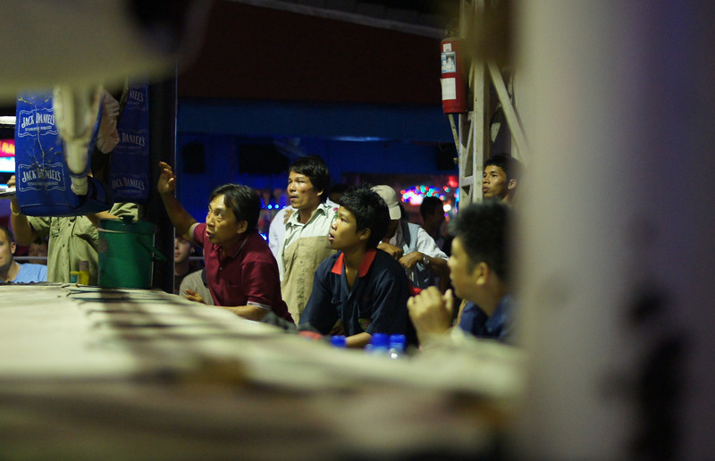 Thai spectators watch with a passion and anxiety of a dedicated fan during a Muay Thai Boxing Match in Chiang Mai, Thailand.