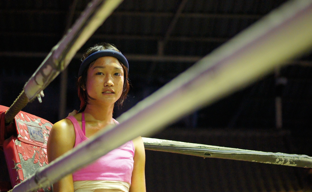 A Thai girl stands in the corner prior to a Muay Thai fight/match in Chiang Mai, Thailand.  Travel photo from Chiang Mai, Thailand.