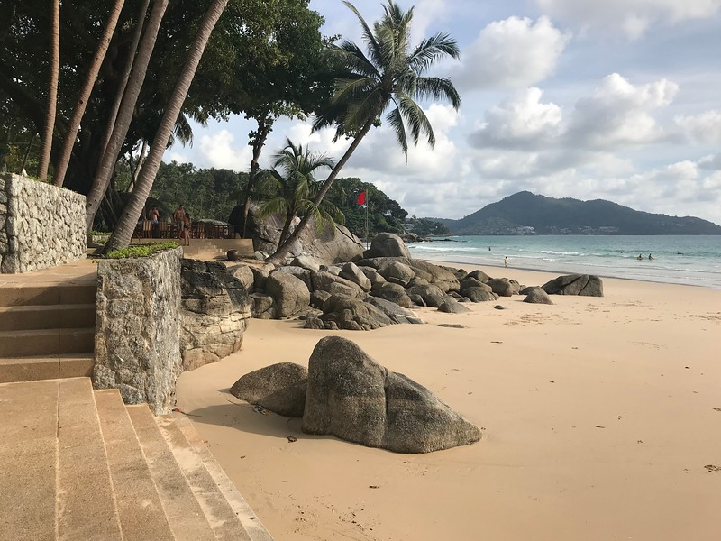 """This is the """"second beach"""" at Amanpuri, that is a """"quiet area or adults only"""" when the tide is up it's all the way to the steps, but at about 11am there is lots of space on the beach. The tables above are the terrace and you can have lunch there."""